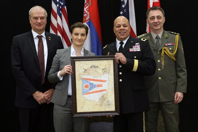 Maj. Gen. John C. Harris Jr. (second from right), Ohio adjutant general, and Serbian Prime Minister Ana Brnabic (second from left) display a gift Harris presented to Brnabi� during an official Serbian delegation visit Jan. 28, 2019, to the Ohio National Guard Joint Force Headquarters located at the Maj. Gen. Robert S. Beightler Armory in Columbus, Ohio. Also pictured are Serbian Ambassador to the U.S. Djerdj Matkovic (left) and Col. Col. Dragan Galic (right), defense, military, naval and air attache with the Serbian Embassy in the U.S. Brnabic led a Serbian delegation to Ohio to explore potential future agricultural and business exchanges, as well as meet with state government officials.