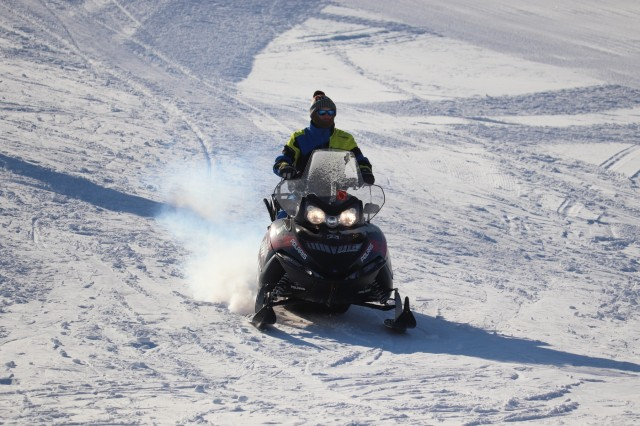 Instructor Mike Nguyen with the Fort McCoy Cold-Weather Operations Course (CWOC) moves equipment with a snowmobile while students practice skiing Jan. 25, 2019, at Whitetail Ridge Ski Area at Fort McCoy, Wis. In addition to skiing, CWOC students are trained on a variety of cold-weather subjects, including snowshoe training as well as how to use ahkio sleds and other gear. Training also focuses on terrain and weather analysis, risk management, cold-weather clothing, developing winter fighting positions in the field, camouflage and concealment, and numerous other areas that are important to know in order to survive and operate in a cold-weather environment. The training is coordinated through the Directorate of Plans, Training, Mobilization and Security at Fort McCoy. (U.S. Army Photo by Scott T. Sturkol, Public Affairs Office, Fort McCoy, Wis.)
