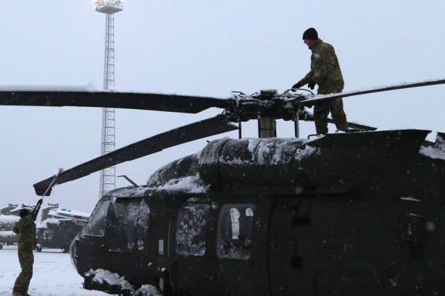 Chief warrant officers two Christopher Okrasinski and Dusty Kahl with A Co., 3rd Assault Helicopter Battalion, 1st Aviation Regiment, 1st Combat Aviation Brigade, 1st Infantry Division, remove snow from a UH-60 Black Hawk helicopter Jan. 30, 2019 at Zeebrugge, Belgium. 1st Combat Aviation Brigade stands ready to support Atlantic Resolve, a key opportunity to train side-by-side with our Allies and partners, and demonstrate U.S. commitment to collective security. (U.S. Army photo by Cpl. Gabrielle Weaver).