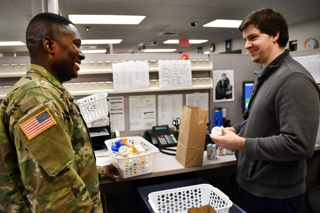 Pharmacist, Joel Hess talks over a medication with Maj. Edward Osei, pharmacy chief in the unit at Kenner Army Health Clinic Jan. 24, 2019. (Photo by Lesley Atkinson, KAHC PAO