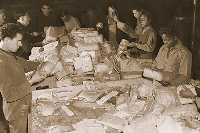 French civilians and soldiers from the 6888th sort mail in the spring of 1945.