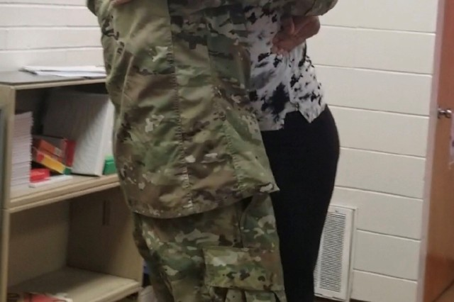 Sgt. 1st Class Jerome Harvey hugs his daughter, Jasmine, after surprising her at school following his return from deployment.