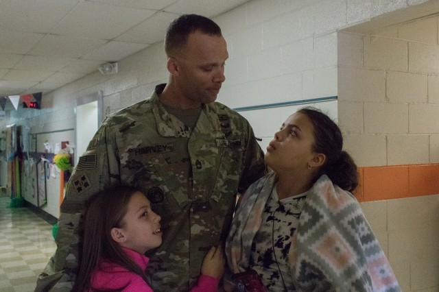 Sgt. 1st Class Jerome Harvey with his daughters, Trinity (left) and Jasmine (right), after surprising them at school following his return from deployment.