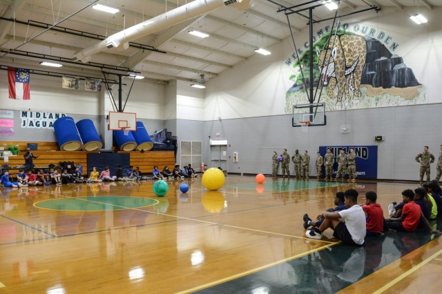 COLUMBUS, Ga. (Feb. 1, 2019) -- Jeremiah Edwards, a physical education teacher at Midland Middle School in Columbus, Georgia, explains the rules of the game cage ball to students and Soldiers from Charlie Company, 1st Battalion, 46th Infantry Regiment, who are located at Fort Benning, Georgia. The Soldiers participated in the gym class as a part of Fort Benning's Partners in Education program Feb. 1, which promotes continued partnerships between the military units and schools within seven school districts of Columbus, Phenix City, Alabama, and the surrounding community. (U.S. Army photo by Megan Garcia, Maneuver Center of Excellence, Fort Benning Public Affairs)