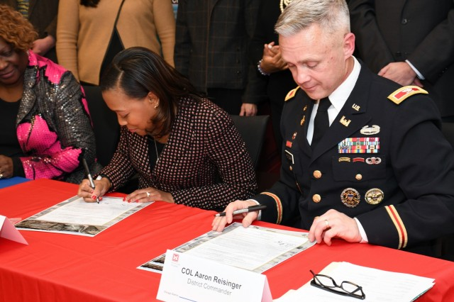 Kari Steele (left), president of the board of commissioners for the Metropolitan Water Reclamation District of Greater Chicago, and Col. Aaron Reisinger (right), commander and district engineer of the U.S. Army Corps of Engineers Chicago District, sign a ceremonial copy of the project partnership agreement between the Corps and MWRD Jan. 31. The MWRD received $33.8 million in federal funds under authority of Section 1043 of the Water Resources Reform and Development Act of 2014, which allows federal funds to transfer through the U.S. Army Corps of Engineers to local sponsors for authorized projects. (U.S. Army photo by Patrick Bray/Released)