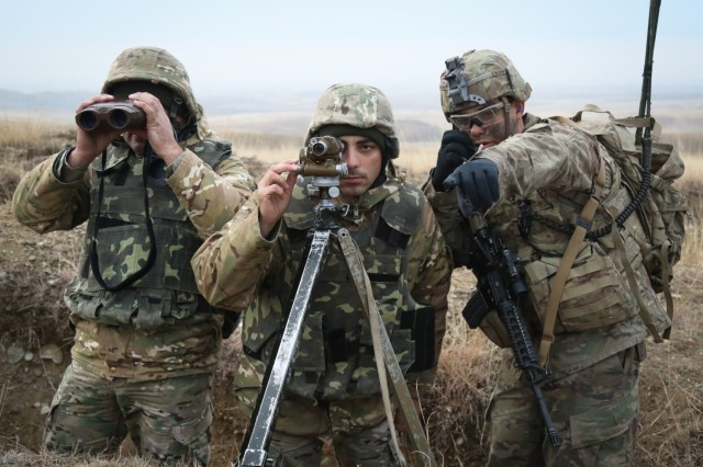 U.S. Army Sgt. Frank Sanchez assigned to red platoon, Cobra Company, 2nd Battalion, 8th Cavalry Regiment, 1st Armored Brigade Combat Team, 1st Cavalry Division and Georgian Soldiers examine the range during a multinational company combined arms live fire event in support of the Georgia Defense Readiness Program at the Vaziani Training Area in Georgia, Dec. 5, 2018. The GDRP is a joint program in which U.S. Army advises, mentor and train Georgian personnel and commanders in order to improve combat readiness.