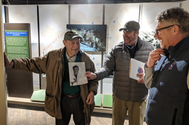 Howard Hall, a 99-year-old World War II veteran, talks about his brother's experience training with the 10th Mountain Division at Camp Hale, Colorado, while his son John hold up a picture of his uncle. Hall and members of his family visited the 10th Mountain Division and Fort Drum Museum on Jan. 29 for a tour with Sepp Scanlin, museum director. (Photo by Mike Strasser, Fort Drum Garrison Public Affairs)