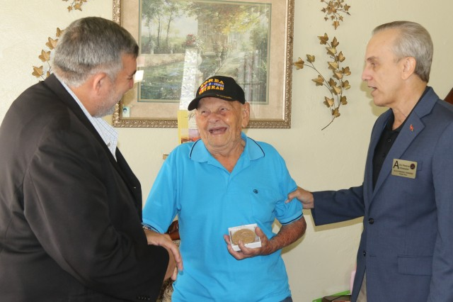 Brig. Gen. retired Fernando Fernandez, U.S. Army Reserve Ambassador in Puerto Rico (right), and Agustin Montañez, Puerto Rico Veterans' Advocate (left), traveled to Aibonito, a mountainous town in the center of the island of Puerto Rico, Feb. 4, to present a replica of the Congressional Gold Medal to Private 1st Class Jose Nicolas Latorre Ortiz, for his service in Korea as member of the 65th Infantry Regiment.