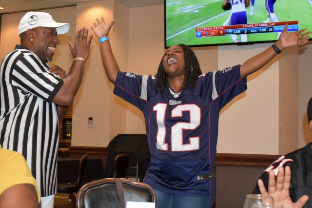 Staff Sgt. Kiki Hill, right, assigned to the 78th Signal Battalion, rejoices at Camp Zama, Japan, Feb. 4, as the New England Patriots score the only touchdown in Super Bowl LIII. Randy Benton, special events coordinator for Camp Zama Family and Morale, Welfare and Recreation, stands left.