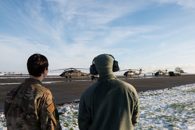 U.S. Air Force Master Sgt. Sherresa Lasseter and Staff Sgt. Brittain Purnell, assigned to the 424th Air Base Squadron, watch the U.S. Army UH-60 Black Hawk helicopters of the 1st Combat Aviation Brigade, 1st Infantry Division, staged on Chievres Air Base, Belgium, Jan. 30, 2019. The brigade will deploy to Germany, Poland, Latvia and Romania for nine months to train with NATO partners in support of Atlantic Resolve.