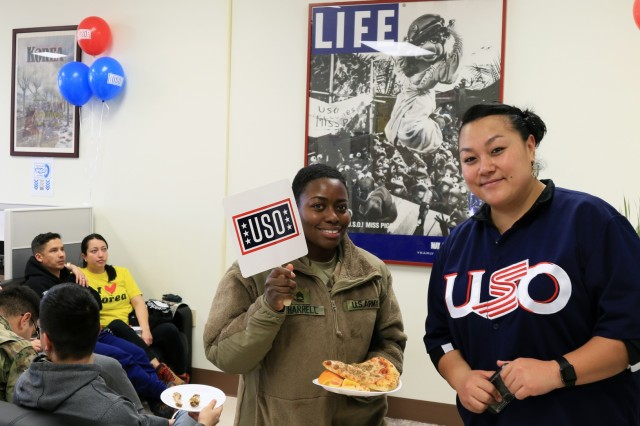 CAMP HUMPHREYS, Republic of Korea - Sonya Tuuao (left), U.S. Army Garrison Yongsan native, United Service Organization facilitator, offers Staff Sgt. Diandra Harrell, New Orleans, Louisiana native, mass communication specialist, 2nd Infantry Division/ROK-U.S. Combined Division, a welcoming home away from home at the U.S. Army Garrison Camp Humphreys' USO. The USO teamed up with the American Red Cross, to provide support and light refreshments during the first-ever 2nd Infantry Division National Anthem live-shot from South Korea during Super Bowl LIII, Feb. 4 at Freeman Hall. With their support, U.S. Army Soldiers were able to enjoy the game thousands of miles from home.