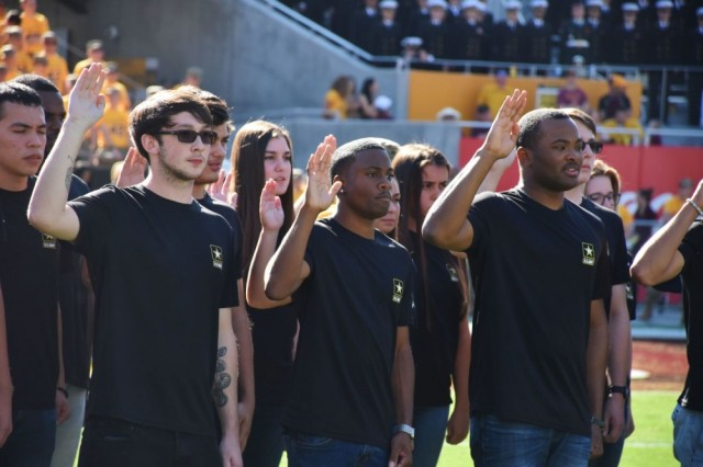 Future Soldiers from the Phoenix Recruiting Battalion participate in a joint-service mass oath of enlistment ceremony during halftime of Arizona State University's Salute to Service college football game between ASU and the University of California, Los Angeles, Nov. 10, in Tempe, Arizona. The Army has been retooling its recruiting strategy that includes emphasis on 22 cities.