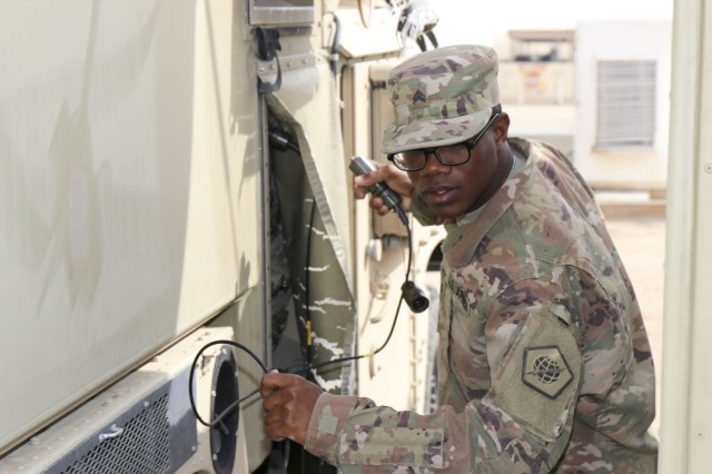 U.S. Army Sgt. Julius Forde, assigned to the 98th Expeditionary Signal Battalion, prepares to check the hookups on a Joint Network Node during the validation exercise at Camp Buehring, Kuwait, January 30, 2019. The 98th Signal Expeditionary Battalion performed the validation exercise to test equipment and ensure proper functionality.  (U.S. Army photo by Capt. Brandon Fambro)