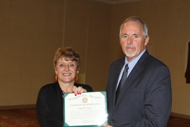 Debra Parra receives a Certificate of Appreciation from Tim Baker, acting division chief, ACC-APG Huachuca Branch, during her retirement ceremony at the Thunder Mountain Activity Center, Fort Huachuca, Jan 29.