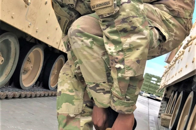 Spc. Walter Thomas, an infantry man with 1st Battalion, 6th Infantry Regiment, puts on one out of four prototypes in the U.S. Army Natick Soldier Research, Development and Engineering Center (NSRDEC) testing of Army hot weather combat boots. The boots were issued for free to approximately 800 Soldiers in 2nd Armored Brigade Combat Team, 1st Armored Division.