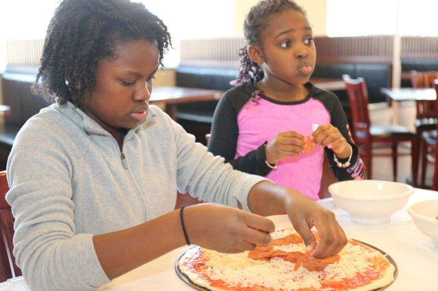 Eleven-year-old Madison Swanigan, left, a member of the Cooking Club at the Sagamihara Family Housing Area School Age Center, carefully places pepperonis on a pizza she and the other members made Jan. 30 during a trip to the SHA Club's Pacific Rim restaurant.
