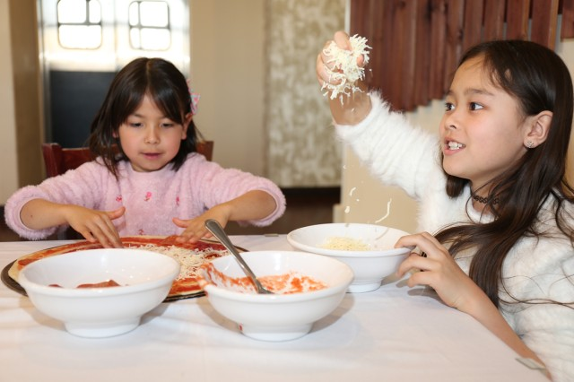 Nine-year-old Erin Hutton, right, grabs a handful of mozzarella cheese to put on a pepperoni pizza she and other members of the Cooking Club at the Sagamihara Family Housing Area School Age Center made Jan. 30 during a trip to the SHA Club's Pacific Rim restaurant.