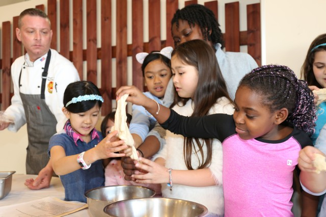 Youth members of the Cooking Club at the Sagamihara Family Housing Area School Age Center put their hands on fresh pizza dough they made together Jan. 30 at the SHA Club's Pacific Rim restaurant. The club members were there to learn how to make pepperoni pizza from scratch, and they later ate their own creations.