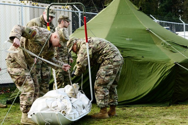 Oregon Army National Guard Spc. Alexander Beglau (left), alongside fellow Soldiers with 2nd Battalion, 162nd Infantry Regiment, 41st Infantry Brigade Combat Team, practices setting up a Canadian Army Reserve tent kit in preparation for the Westie Avalanche Exercise, Jan. 25, 2019, at the Chilliwack Armoury, in Chilliwack, British Columbia, Canada.
