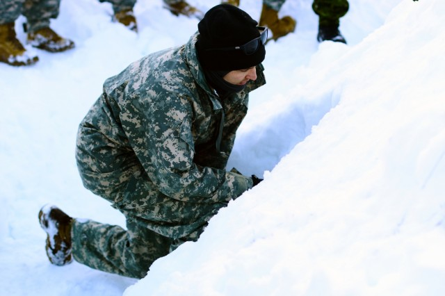 Oregon Army National Guard Spc. Dylan Williams, with Headquarters and Headquarters Company, 2nd Battalion, 162nd Infantry Regiment, 41st Infantry Brigade Combat Team, looks inside the opening of a snow shelter built by Canadian Rangers to learn techniques for building his own shelter to sleep in during Westie Avalanche Exercise, Jan. 26, 2019, at E.C. Manning Park, British Columbia, Canada.