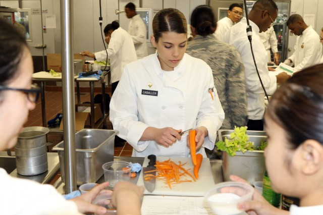 The Adopt an Installation culinary program brings civilian executive chef expertise to Army training. Spc. Beatriz Caballer, a culinary specialist assigned to 593rd Expeditionary Sustainment Command, helps prepare a recipe designed by executive chef Mike Speranza during training on Joint Base Lewis-McChord.