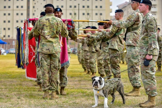 CAMP HUMPHREYS, Republic of Korea -- Leaders from the 3rd Armored Brigade Combat Team, 1st Armored Division uncase battalion colors during a transfer of authority ceremony 1st ABCT, 3rd Infantry Division, at Camp Humphreys, October 22, while the ABCT mascot, Pvt. Tank Chester, stands proud. 3rd ABCT will serve as the rotational brigade under the 2nd Infantry Division/ROK-U.S. Combined Division. This marks the first time that 1AD Soldiers have deployed to Korea. (U.S. Army Photo by Mr. Pak, Chin U., 2ID/RUCD Public Affairs)