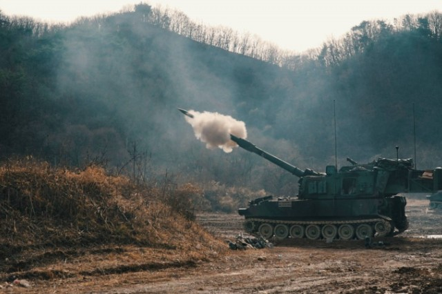 "CAMP HOVEY, Republic of Korea - A M109A6 Paladin fires a 155mm inert training round during the 4th Battalion, 1st Field Artillery Regiment ""Defender,"" 3rd Armored Brigade Combat Team, 1st Armored Division (Rotational) Table VI Gunnery at St. Barbara Range Dec. 5. Table VI Gunnery is an annual training requirement for Field Artillery units that certify individual howitzer crews and platoon Fire Direction Centers. This training focuses on overall readiness and maintaining Field Artillery core competencies at the section level. (U.S. Army photo by 1st Lt. Sean M. Kealey)"