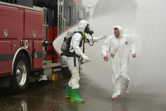 Members of the Richmond, California Fire Department escort and assist simulated casualties through a fire hose sprayed chemical decontamination workstation during the Bay Area training exercise, at Richmond, California, Jan. 31, 2019. National Guard civil support teams worked with local agencies in a series simulated chemical incidents around the San Francisco Bay area as part of BAYEX, a week-long training exercise designed to bring multiple response agencies together to enhance interoperability during large-scale disasters.