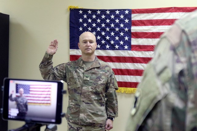 Col. Hugh Mccallum repeats after Brig. Gen. Clint Walker, commanding general of 184th Sustainment Command, while being sworn in during his promotion ceremony at Camp Arifjan, Feb. 2, 2019. (U.S. Army National Guard photo by Sgt. Connie Jones)