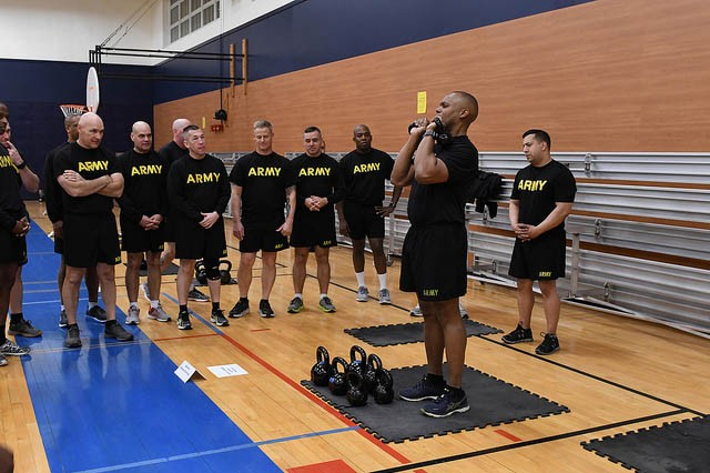 Combined Arms Center Special Troops Battalion Command Sgt. Maj. Kevin Campbell demonstrates the overhead push press station for the group of command sergeants major during physical training on the second day of the Combined Arms Center Command Sergeant Major Forum Feb. 6 at Harney Sports Complex. The CSMs were participating in PT focused on preparing Soldiers for the new Army Combat Fitness Test that is currently being implemented across the Army. The two-day CAC CSM Forum brought CSMs from the CAC Center's of Excellence and schools together to discuss enlisted education in the Army. Photo by Tisha Swart-Entwistle Combined Arms Center Public Affairs.