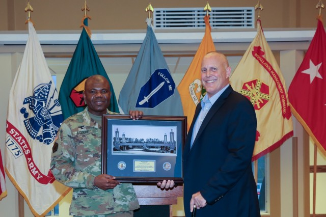 FORT BENNING, Ga. (Feb. 8, 2019) - Chaplain (Col.) Dawud Agbere, left, presents Retired Col. Timothy Karcher with a commemorative photo thanking him for serving as guest speaker during a breakfast prayer event. The chaplains of the Maneuver Center of Excellence Religious Support Office hosted a special breakfast in observance of National Day of Prayer Feb. 8 at the Benning Club at Fort Benning, Georgia. Karcher spent nearly 26 years in the military. In 2009, during his third combat deployment, Karcher was leading a mounted patrol when his vehicle was struck by an explosive device, which penetrated the vehicle's armor and destroyed his legs. (U.S. Army photo by Markeith Horace, Maneuver Center of Excellence, Fort Benning Public Affairs)