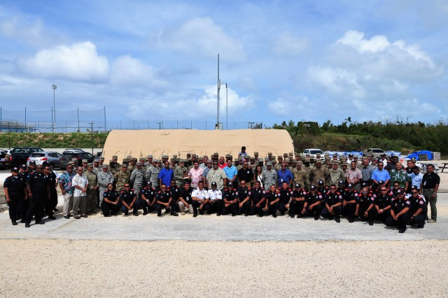 SAIPAN, Commonwealth of the Northern Mariana Islands (Feb. 6, 2019) - Rear Adm. Shoshana Chatfield, commander, Joint Region Marianas and commander, Joint Task Force West, and the Commonwealth of the Northern Mariana Islands Gov. Ralph Deleon Guerrero Torres are joined by Joint Task Group Engineer and Saipan first responders for group photo after the closing ceremony for Joint Task Group Engineer in Saipan, CNMI. The ceremony was held to mark theend of Department of Defense relief and recovery efforts in support of the Federal Emergency Management Agency and CNMI's civil and local authorities from the devastating impacts of Super Typhoon Yutu, which hit the commonwealth Oct. 25, 2018