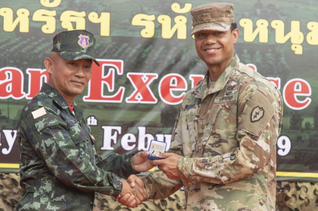 Col. Chitsanupong Rodsiri, the Deputy Commanding General for 2nd Infantry Division King's Guard, Royal Thai Army, and Maj. Williams formally exchange gifts between the two army units during the Hanuman Guardian closing ceremony, Feb. 7, 2019, at Camp Nimman Kolayut, Thailand. Hanuman Guardian 2019 was a training exercise with the Royal Thai Army designed to enhance military-to-military partnerships, interoperability and mission readiness.
