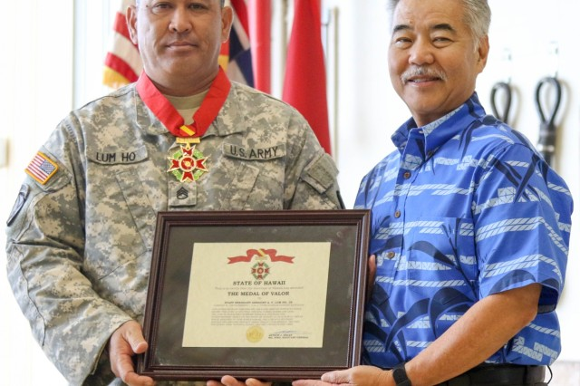 Governor David Ige presents State Medal of Valor recipient, Staff Sergeant Gregory A.Y. Lum Ho, Jr., with a framed award certificate during a ceremony held on February 9, 2019, at Wheeler Army Airfield, Hawaii.  Staff Sgt. Lum Ho was awarded the State Medal of Valor for ignoring substantial risk to his own life to ensure the rescue of a family of six while supporting Hawaii National Guard response efforts to Tropical Storm Lane on August 23, 2018,