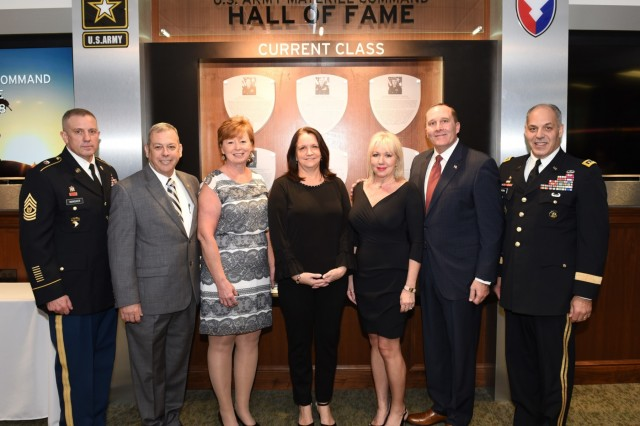 Retired Command Sergeants Major Daniel Elder, second from left, and Ronald Riling, second from right, are honored at an Army Materiel Command Hall of Fame Induction Ceremony Feb. 5 at AMC headquarters, Redstone Arsenal, Ala. With them are, from left, AMC Command Sgt. Maj. Rodger Mansker, Gloria Elder, Susan Perna, Melinda Riling and AMC commander Gen. Gus Perna, who hosted the ceremony. (U.S. Army Photo by Doug Brewster)