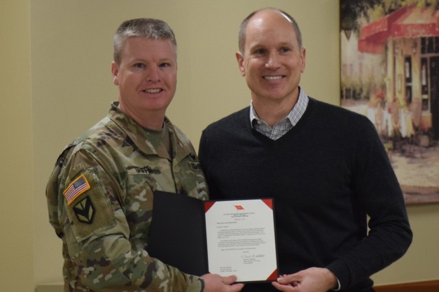 TACOM Command Sgt. Maj. Ian Griffin presents a 2-star note from Maj. Gen. Daniel Mitchell to Jason Hanson.
