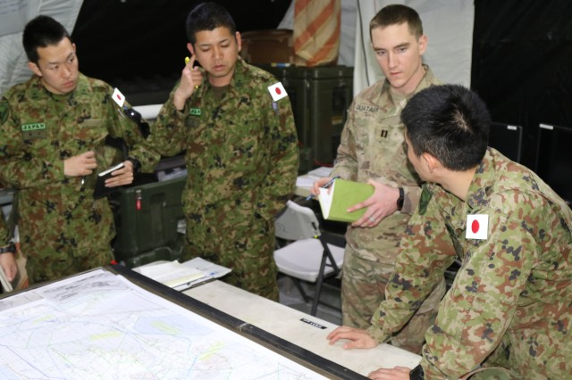 "Capt. Alexander Quataert, 1st Stryker Brigade, 25th Infantry Division, and soldiers from the 72nd Tank Regiment, Japanese Ground Self Defense Force, analyze a map of desert terrain in preparation for their February rotation at the National Training Center, Jan. 29. The two units are joining together, along with other Army units, Marines, and airmen from throughout the world to form ""Combined Joint Task Force Arctic Wolves."" The CJTF includes more than 500 Japanese soldiers, the most to ever participate in an overseas joint training exercise. The NTC rotation officially started Feb. 4."
