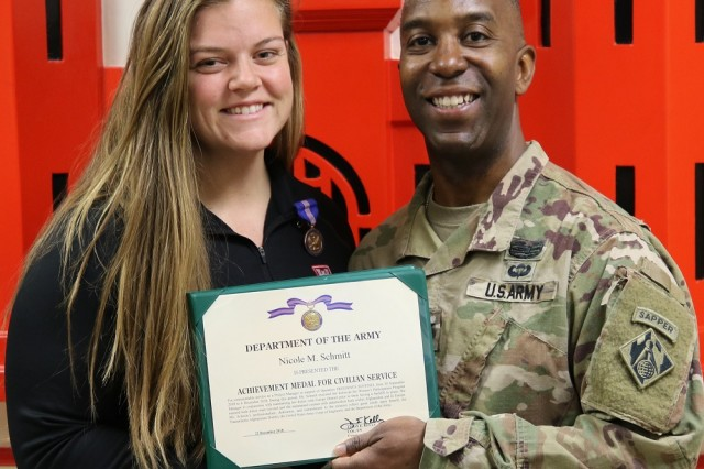 Nicole Schmitt receives an Achievement Medal for Civilian Service from District Commander, Col. Jason Kelly.