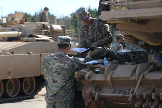 Spc. David Cho, gunner (left), Pfc. Skylar Carnaghi, driver (right) assigned to 3rd Battalion, 67th Armored Regiment, 2nd Armored Brigade Combat Team, 3rd Infantry Division, execute Preventative Maintenance Checks and Services on an M1A1 Abrams Tank after returning from Hound Focus at Fort Stewart, Ga. Feb. 4, 2019. (U.S. Army photo by Spc. Andres Chandler/released)
