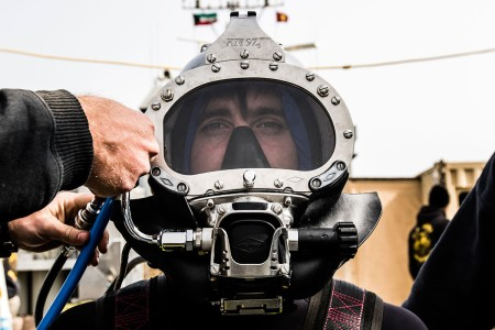 A second class diver assigned to the 86th Engineer Dive Detachment, waits as his equipment is checked before conducting a dive near Kuwait Naval Base, Kuwait, Jan. 22, 2019.  The 86th EDD conducted dive supervisor training and qualification to increase the number of Soldiers qualified to act as dive supervisors as well as  increase their units overall readiness.