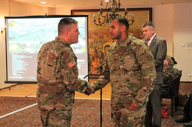 Col. Adam J. Boyd, USAG Bavaria commander, awards Sgt. Jordan Quiernan, 3rd Squadron, 2nd Cavalry Regiment, with the Army Achievement Medal Feb. 12 for outstanding work as a unit environmental officer.