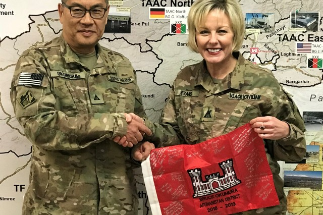 """Bruce Okumura, Deputy Chief of Contracting receives an autographed miniature Corps Flag from the PPMD group as a """"Thank You"""" for his outstanding efforts in support of the program in theater."""