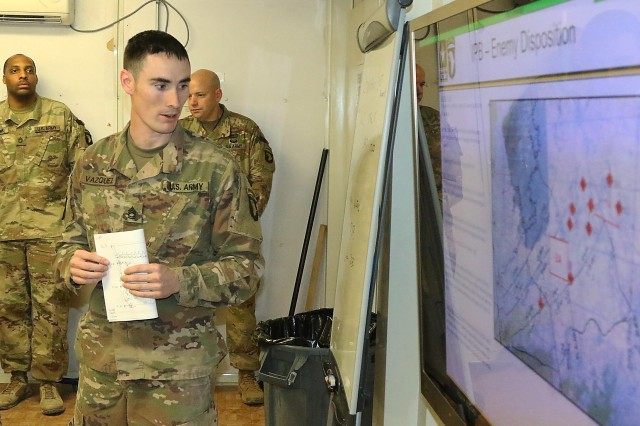 Sgt. 1st Class Jonathan Vazquez gives his presentation on a fictitious operation Feb. 12, the night prior to graduation at Bagram Airfield, Afghanistan. (Photo by Jon Micheal Connor, Army Public Affairs)