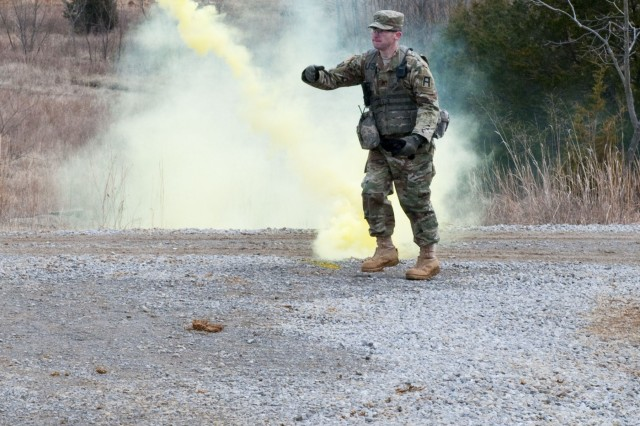A 1st Battalion, 409th Brigade Engineer Battalion observer coach/trainer tosses an M18 yellow smoke grenade to simulate a chemical attack during a dismounted live fire lane for Soldiers from 818th Maintenance Company and 826th Ordnance Company, Jan. 27, at Fort Knox. (U.S. Army photo by Sgt. 1st Class Gary J. Cooper/4th Cavalry Multi-Functional Training Brigade)
