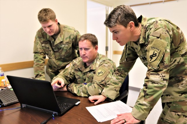 Pvt. Blake Lapel, Command Sgt. Maj. Don Samuelson, and Capt. Shannon Woodman with the Army Reserve's 432nd Civil Affairs Battalion of Green Bay, Wis., discusses a training event Feb. 8, 2019, at Fort McCoy, Wis., during Command Post Exercise-Functional 19-10. Approximately 300 Soldiers with civil affairs, psychological operations, and information operations units trained in the U.S. Army Civil Affairs and Psychological Operations Command- centric exercise that was conducted on post from Jan. 22 to Feb. 11. (U.S. Army Photo by Scott T. Sturkol, Public Affairs Office, Fort McCoy, Wis.)