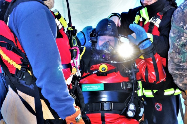 A firefighter finishes putting on his equipment as he prepares to dive under the ice Feb. 6, 2019, at Big Sandy Lake on South Post at Fort McCoy, Wis. About a dozen firefighters with the Directorate of Emergency Services Fire Department practiced ice diving as part of the Fort McCoy dive team. Overall, the firefighters completed four days of training related to ice diving that also included classroom time and practice at the pool at Rumpel Fitness Center. Fort McCoy built the dive team capability eight years ago and the team has responded to real-world emergencies, including recently to an emergency in Sparta, Wis. (U.S. Army Photo by Scott T. Sturkol, Public Affairs Office, Fort McCoy, Wis.)