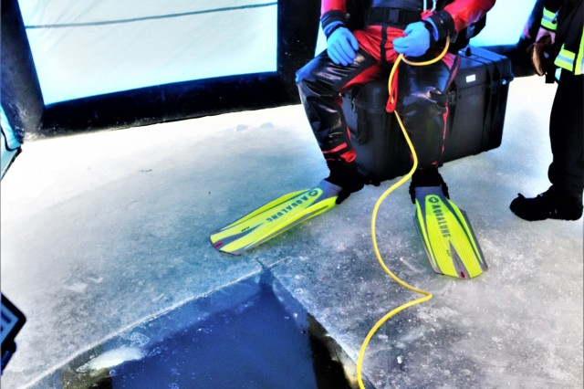 A firefighter wearing a full diving suit and related equipment prepares to dive under the ice Feb. 6, 2019, at Big Sandy Lake on South Post at Fort McCoy, Wis. About a dozen firefighters with the Directorate of Emergency Services Fire Department practiced ice diving as part of the Fort McCoy dive team. Overall, the firefighters completed four days of training related to ice diving that also included classroom time and practice at the pool at Rumpel Fitness Center. Fort McCoy built the dive team capability eight years ago and the team has responded to real-world emergencies, including recently to an emergency in Sparta, Wis. (U.S. Army Photo by Scott T. Sturkol, Public Affairs Office, Fort McCoy, Wis.)