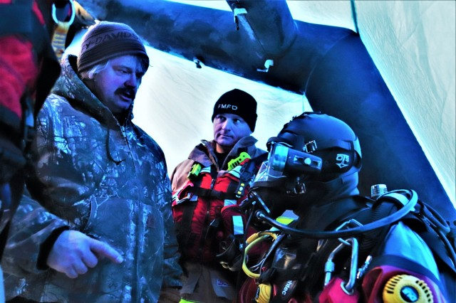 Instructor Jeff Zilliox (left) with the Marineland Dive Center of Onalaska, Wis., gives a firefighter direction during ice diving training Feb. 6, 2019, at Big Sandy Lake on South Post at Fort McCoy, Wis. About a dozen firefighters with the Directorate of Emergency Services Fire Department practiced ice diving as part of the Fort McCoy dive team. Overall, the firefighters completed four days of training related to ice diving that also included classroom time and practice at the pool at Rumpel Fitness Center. Fort McCoy built the dive team capability eight years ago and the team has responded to real-world emergencies, including recently to an emergency in Sparta, Wis. (U.S. Army Photo by Scott T. Sturkol, Public Affairs Office, Fort McCoy, Wis.)
