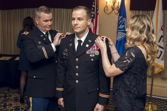 Colonel Michael Parent (c.) stands at attention while PM AESIP Colonel RJ Mikesh (l.) and his wife (r.) replace Lieutenant Colonel with Colonel rank insignia on his uniform during the promotion ceremony portion of the event.