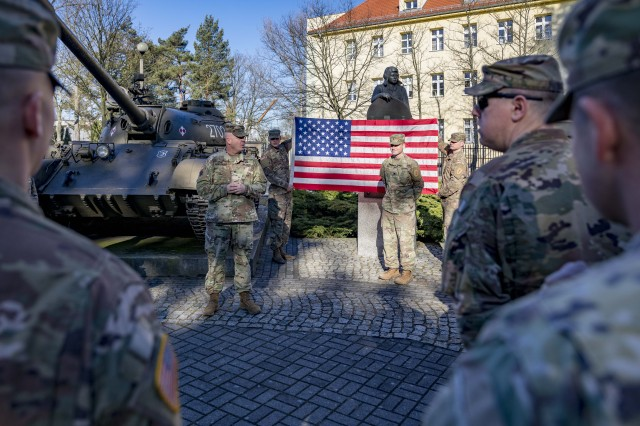ZAGAN, Poland (Feb. 16, 2019) --  Col. Charles S. Armstrong, commander, 1st Armored Brigade Combat Team, 1st Infantry Division speaks on behalf of Spc. Jeb Stuart Dickey, commanders driver and motor transport operator, Headquarters and Headquarters Company, 1ABCT, during his reenlistment ceremony, Feb. 16. Dickey, who hails from Stillwater, Oklahoma, spent two years with the Oklahoma National Guard before enlisting on active duty two years ago. (U.S. Army photo by Sgt. Thomas Mort)